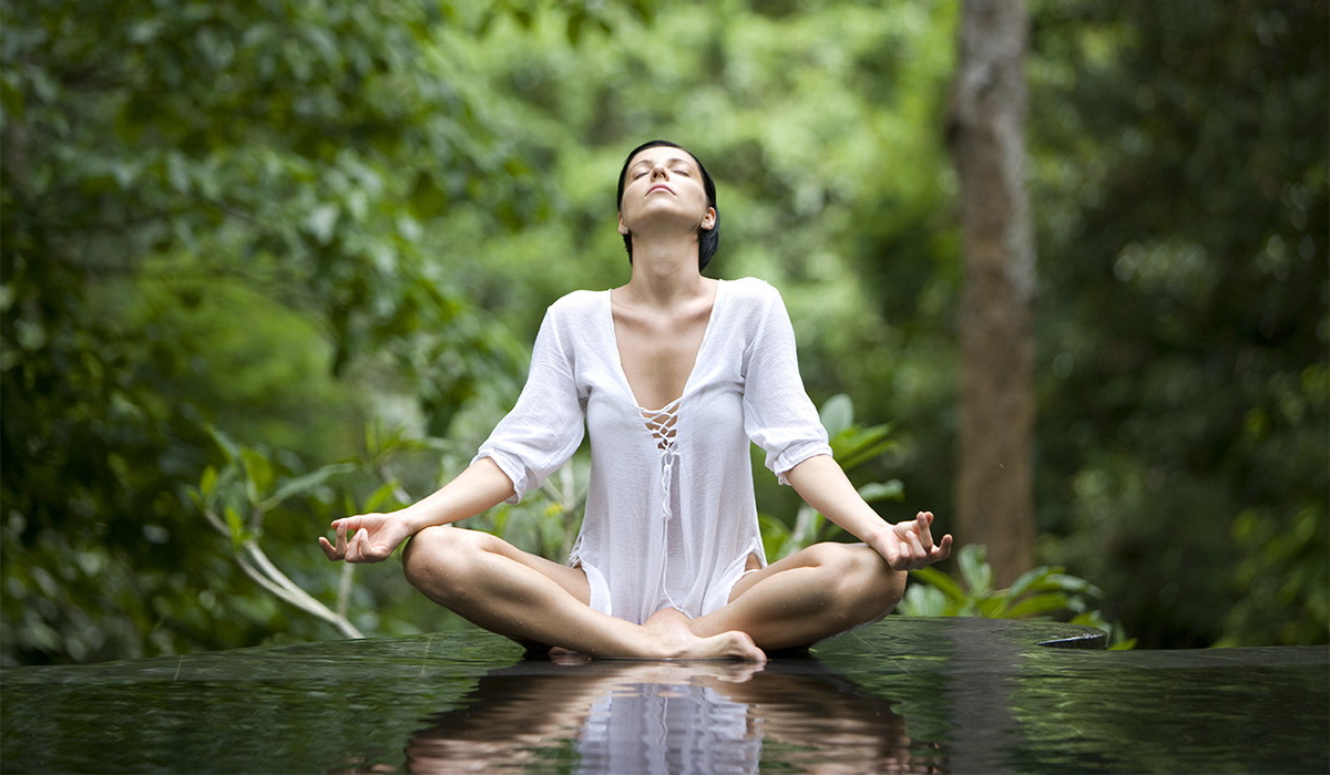 A woman relaxing and meditating in a forest